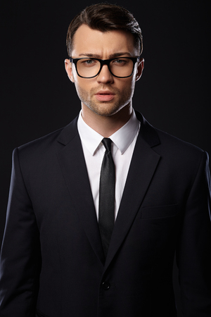 man in suite: Handsome businessman wearing suite, black background. Glasses. Stock Photo