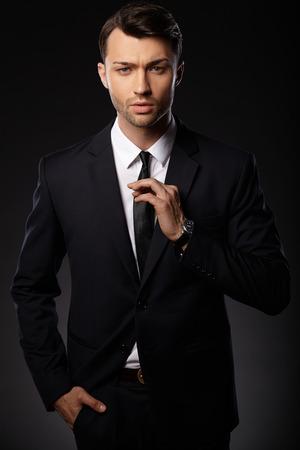 black tie: Portrait of young business man. Black background.