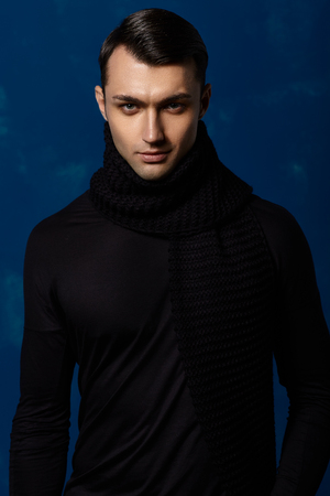 Fashion young man in scarf on blue background.