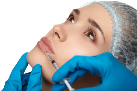 Portrait of young woman getting cosmetic injection of botox, isolated over white background. Banco de Imagens