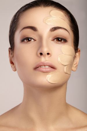 applying: Young woman with cosmetic foundation on a skin. Stock Photo