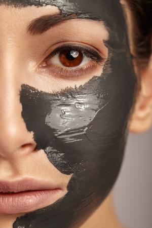 顔のマスクを持つ美しい女性。
