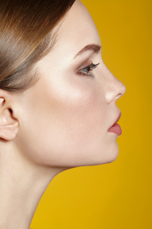 Portrait of beautiful young woman with clean face. Yellow background. Banco de Imagens