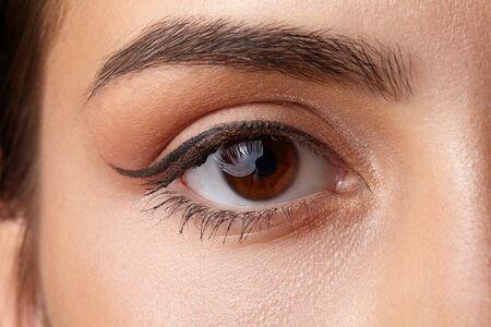 brown eye: Female brown eye close-up. Light make-up arrow. Stock Photo