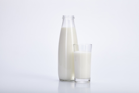 Open a bottle and a glass of milk on a white background.