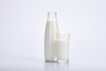 verre de lait: Ouvrez une bouteille et un verre de lait sur un fond blanc.