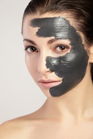 antifaz: Mujer hermosa joven en una máscara para la cara del barro negro terapéutico. Tratamiento de spa. Foto de archivo
