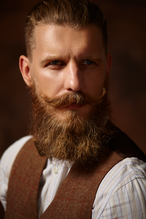 model portrait: Close portrait of a bearded man in a shirt and a brown vest on a brown background.