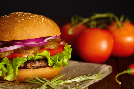 burger: Fresh burger with lettuce, onions, tomatoes, pickles and beef steak on a wooden board. Stock Photo