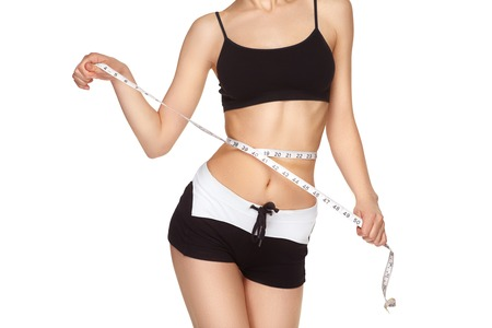 Young slim girl measuring waist measuring tape. Cropped image. Banco de Imagens