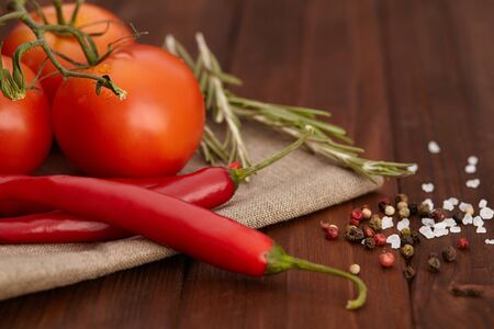 tomatto: Herbs and spices. Red chili pepper, salt, tomatto and rosemary on wooden board. Stock Photo