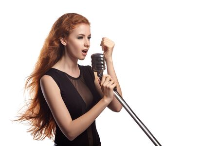 red hair girl: Young beautiful girl with flowing red hair singing into retro microphone.