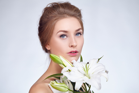 flower: Portrait of beautiful girl with make-up arrows and red lips. White lilies in hands.