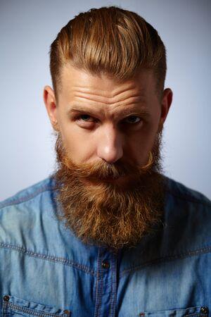 hombre con barba: Retrato de un hombre brutal con barba y bigote con la cabeza inclinada en una camisa de mezclilla sobre un fondo gris.