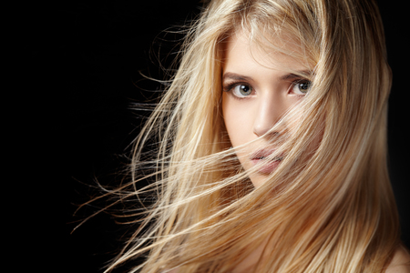 nude blonde: Close portrait of a beautiful young blonde woman with flying hair on a black background.