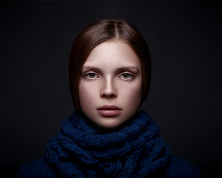 Art portrait of a beautiful young girl with freckles in a sweater and scarf on a dark background. Banco de Imagens