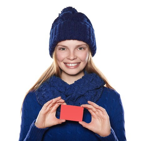 sweater girl: Young girl in a blue sweater, scarf and knit hat holding a card and smiling.