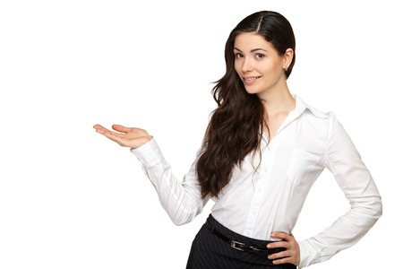 pointing at: Young business woman is pointing with his hand and smiling. White background. Stock Photo