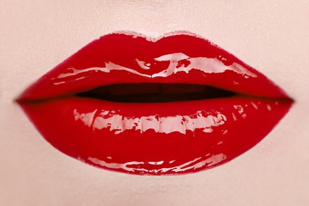 gloss: Close-up view of female wearing red lipstick with mouth open.