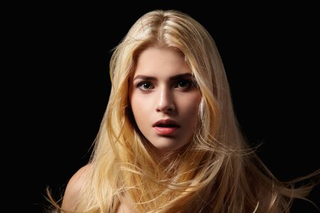 flying hair: Portrait of blonde girl with flying hair on a black background.
