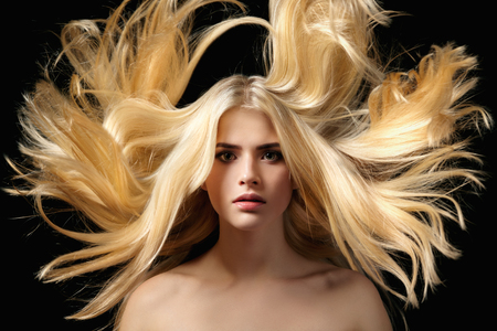 adult nude: Portrait of a beautiful young blonde girl with flying hair on a black background.