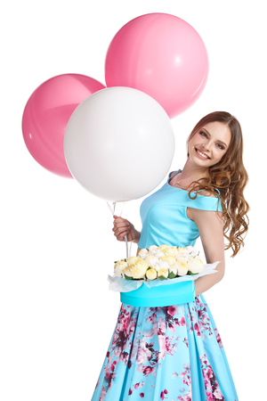 Beautiful young girl in a bright blue dress on a white background holding balloons, a box with paper flowers and laughs.