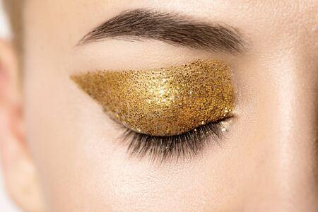 and eyelid: Close up female closed eye with bright gold glitter on the eyelid. Macro. Stock Photo