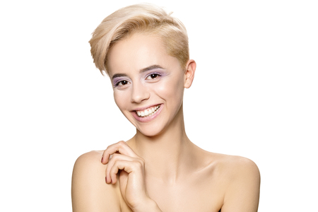 broadly: Beautiful young girl with white hair and short hair looking into the camera and smiles broadly. Stock Photo