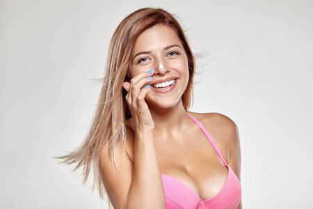 gets: Attractive girl in pink swimsuit gets on the nose cream and smiles.