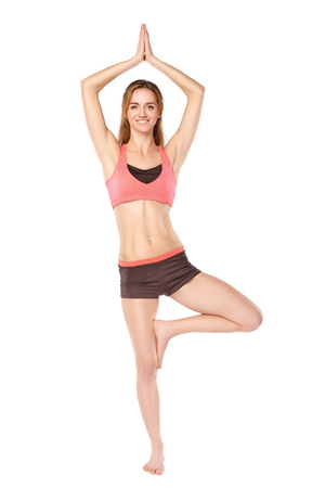 in unison: Young sporty girl practicing yoga. White background. Stock Photo