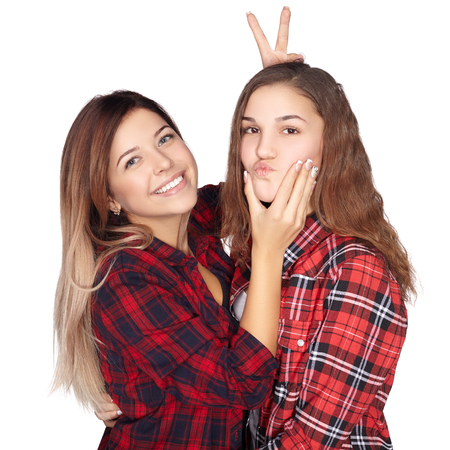 Attractive sisters goofing around and smiling at the camera. White background. Banco de Imagens