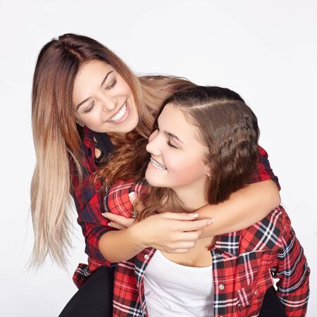 Two sisters having fun and laughing. White background.