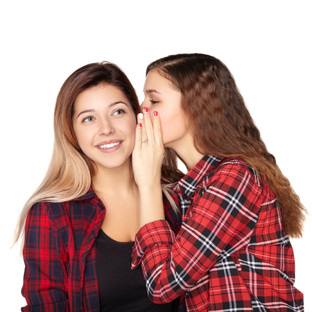 Young attractive girl whispering in the ear of his sister.