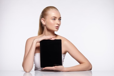 Beauty portrait of attractive young girl with natural makeup. Girl holding tablet.