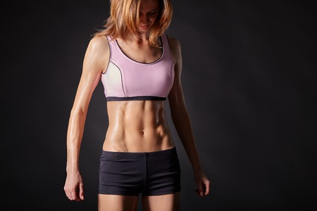 Athletic strong and beautiful female body. Black background.