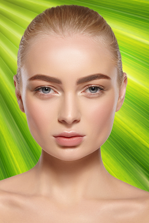 Close-up portrait of attractive girl with natural makeup on a background of green tropical leaf. Banco de Imagens