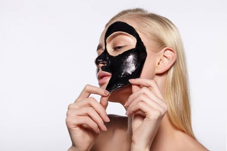 A young girl takes a black mask from her face. The gray background. Banco de Imagens