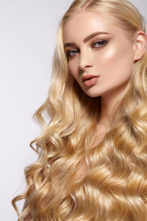 Portrait of attractive girl with blond curls. The gray background.