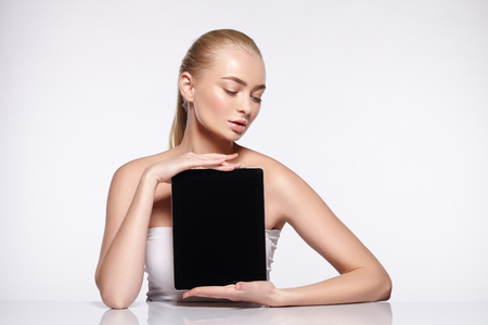 Attractive young blonde girl with natural makeup and curls holds the tablet.