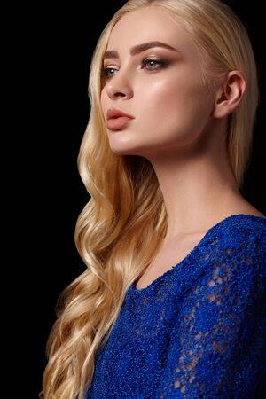 Portrait of a beautiful blonde girl with curly hair in a bright blue dress on black background Banco de Imagens