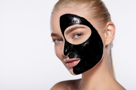 Close-up portrait of attractive girl with black cosmetic mask on her face.
