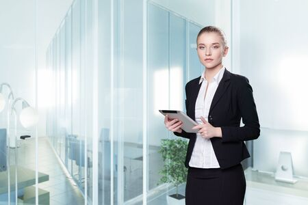 Young attractive woman in a business suit with tablet in office.