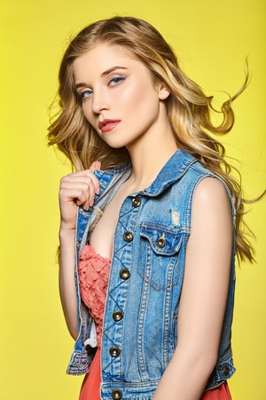 Attractive young girl with long flowing hair on a bright yellow background. Reklamní fotografie
