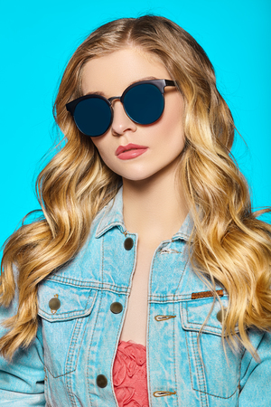Young girl with curly hair and glasses on a blue background.