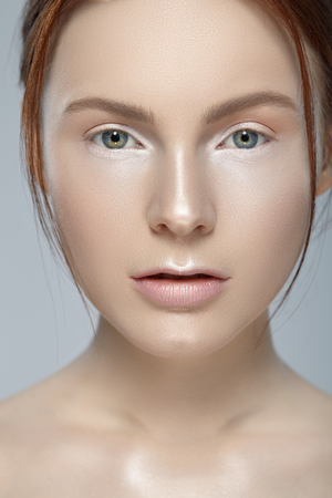 Close-up beauty portrait of attractive girl with perfect skin and natural makeup on gray background. Banco de Imagens