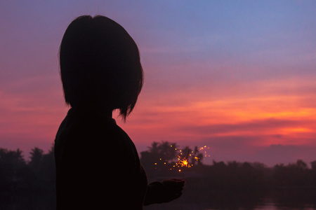 Silhouette emotional alone celebrate the lonely under the sunset with a little firework. Stock Photo