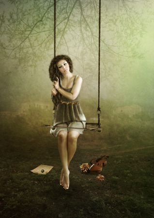 Young violinist girl sitting on swing outdoors photo