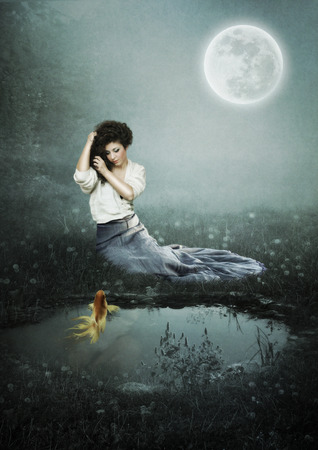The young girl with golden fish sitting in the moonlight near the pond photo