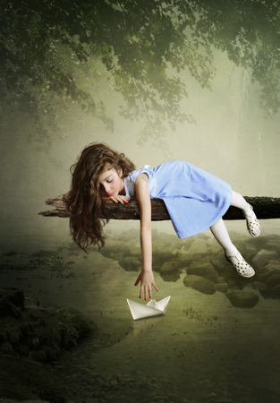 Girl with long hair lying on the tree and playing with paper boats photo