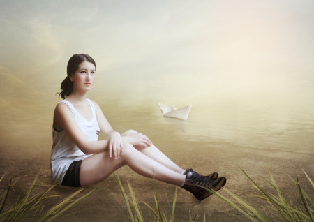 Young girl sitting on the river bank and dreaming photo
